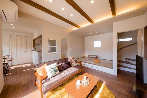 床と同色の梁を間接照明で照らした暖かい雰囲気のリビング。段差に腰かけてくつろげる 小上がりおしゃれ畳+お部屋をすっきり床下収納スペース♪