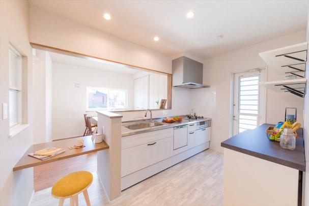 白を基調にした明るいキッチン。キッチン横には2人掛けカウンターを設置しました。お茶を飲んだり、家事スペースなど様々な用途に使えます。